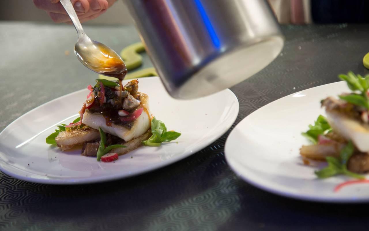 Zoom sur le dressage de deux assiettes gastronomiques dans le restaurant étoilé Coté Cuisine